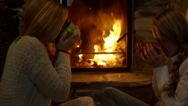 vidéos et rushes de young women sitting by fireplace and having drink - chalet
