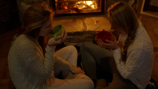 Young women sitting by fireplace and having drink