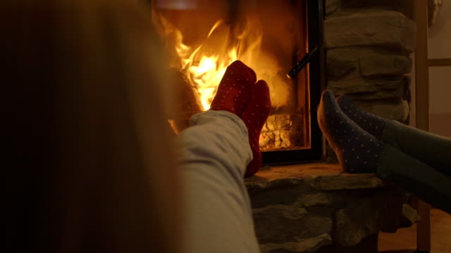 young women sitting by fireplace and having drink - legs crossed at ankle stock videos and b-roll footage