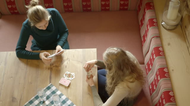 Young women sitting by table and playing cards