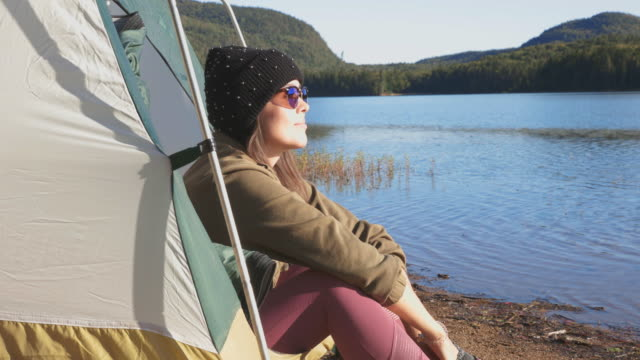 young women sitting in her tent by the lake in camping - eyewear stock videos & royalty-free footage