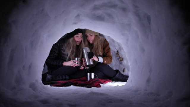 young women sitting in igloo pouring hot beverage into mug - igloo stock videos & royalty-free footage