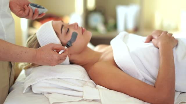 vídeos y material grabado en eventos de stock de mujeres jóvenes spa tratamiento cepillo máscara facial en la cara en el centro de spa - spa treatment