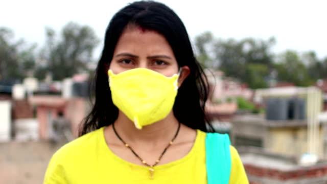stockvideo's en b-roll-footage met jonge vrouwen die covid-19, new delhi, india tegenhouden - bord bericht