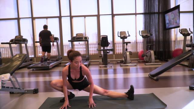 junge frauen strecken sich im fitnessstudio - only young women stock-videos und b-roll-filmmaterial