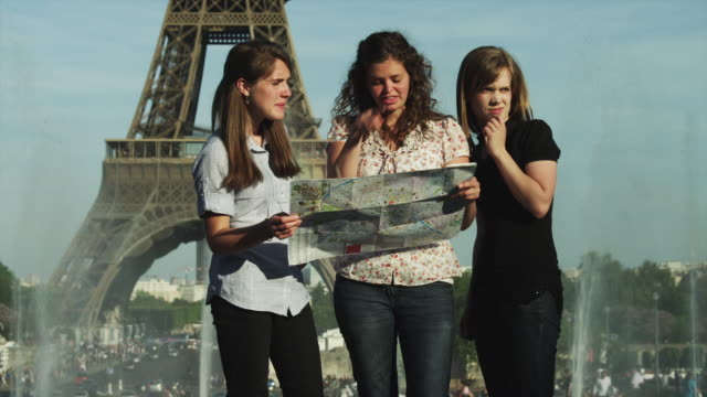 MS Young women studying map in front of Eiffel Tower / Paris, France
