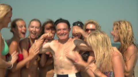 vídeos y material grabado en eventos de stock de slo mo ms zi young women surrounding and embracing elderly man flexing muscles on beach, jacksonville, florida, usa - 18 19 años