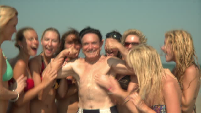 SLO MO MS ZI Young women surrounding and embracing elderly man flexing muscles on beach, Jacksonville, Florida, USA