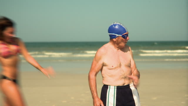 vídeos de stock, filmes e b-roll de slo mo ms young women surrounding and embracing elderly man standing on beach, jacksonville, florida, usa - rodeando