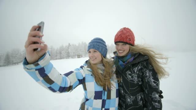 young women taking selfie in snow - ski jacket stock videos & royalty-free footage