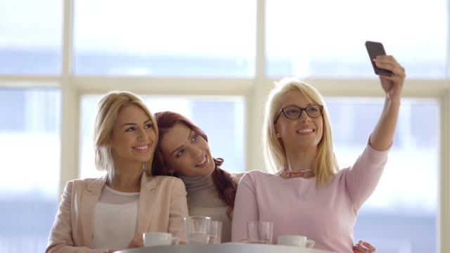 Young women taking Selfie, laughing in coffee shop.