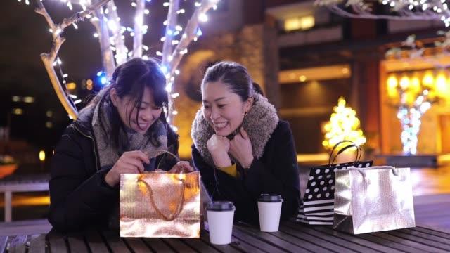 買い物の後何を買ったか話している若い女性 - 歯を見せて笑う点の映像素材/bロール