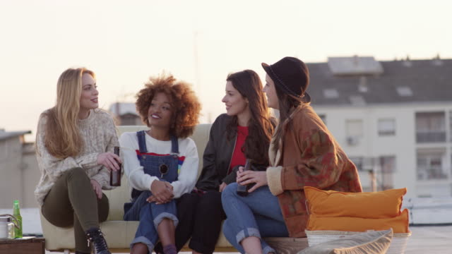 Young women talking during rooftop party in summer