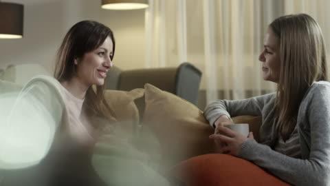 vídeos y material grabado en eventos de stock de mujeres jóvenes hablando con sofá - two people