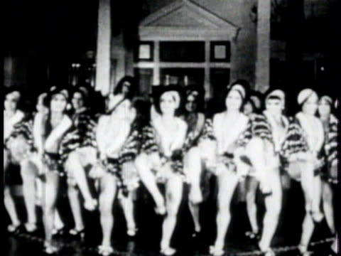 vídeos de stock, filmes e b-roll de young women tap dancing on dance floor w/ band bg, neon 'cotton club' sign, women dancing low stage, edward kennedy 'duke' ellington, more women... - 1920