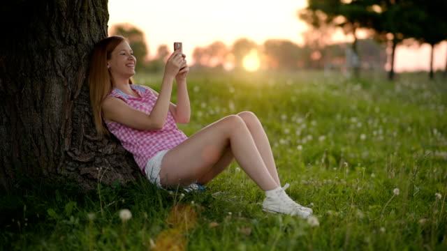 junge frauen sms ihr freund und genießen sonne - shorts stock-videos und b-roll-filmmaterial