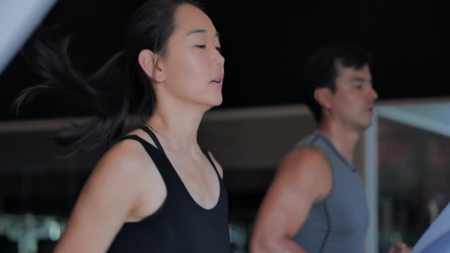 若い女性はジムでコーチと一緒にトレーニングをしています。運動、フィットネス、健康的なライフスタイルのためのトレッドミルのコンセプトで実行されている人々。スポーツ - コーチン� - ダイエット点の映像素材/bロール