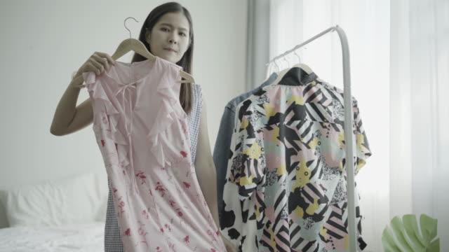stockvideo's en b-roll-footage met jonge vrouwen die proberen gekleed thuis. - jurk