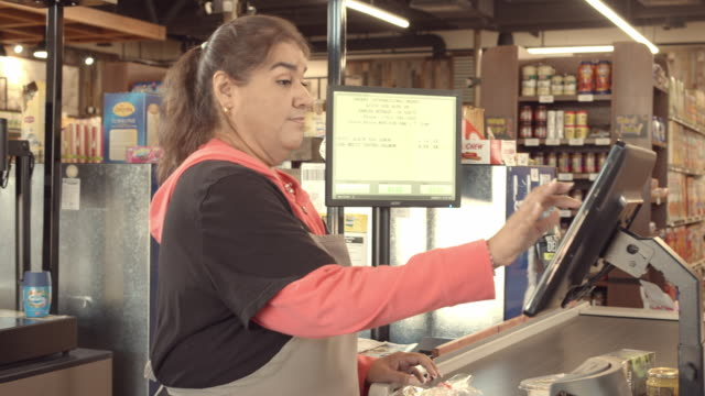 DS young women unloads shopping cart at checkout while cashier enters each item into computer screen