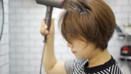 Young women use hair dryer