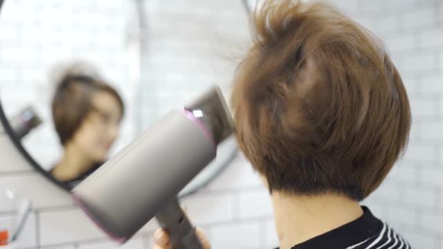 vídeos de stock e filmes b-roll de young women use hair dryer - estilo de cabelo