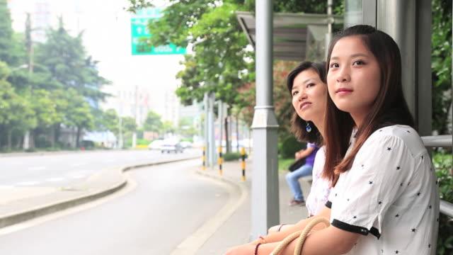 young women using a smartphone in the train - バス停留所点の映像素材/bロール