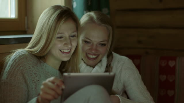 Young women using digital tablet in chalet