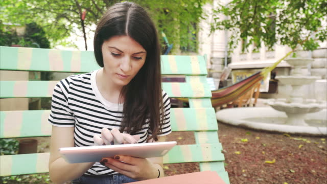 young women using digital tablet in the garden. - giardino domestico video stock e b–roll