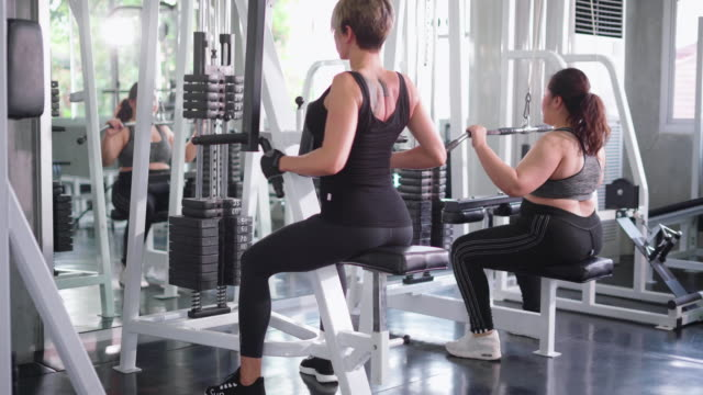 young women using exercise machine in gym - lateral pull down weights stock videos & royalty-free footage
