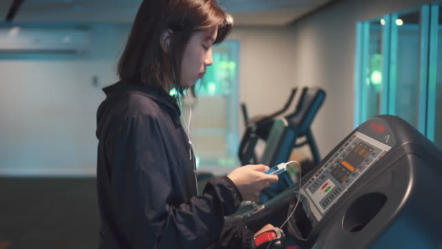 Young Women using smart phone at gym