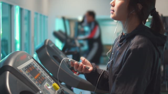 Young women using smart phone at gym,Slow motion