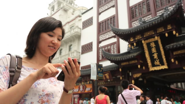 young women using smartphone in yuyuan tourist mart - non western script stock videos & royalty-free footage