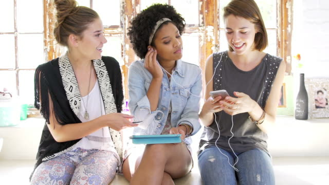 Young women using smartphones and tablet and sharing headphones