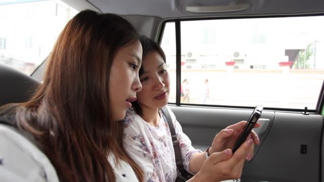 young women waiting for bus - 2人点の映像素材/bロール