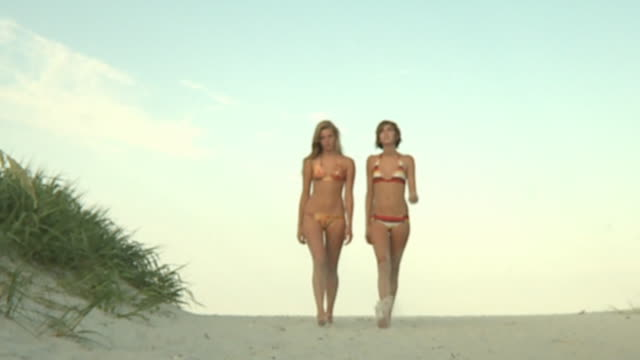 slo mo ms pan la young women walking on beach, jacksonville, florida, usa - ビキニ点の映像素材/bロール