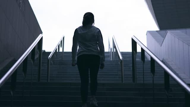 junge frauen gehen die treppe einsamkeit hinauf - moving up stock-videos und b-roll-filmmaterial