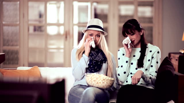 Young women watching a movie together and crying