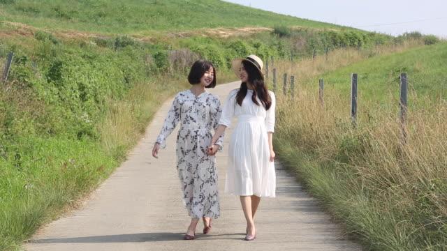 vídeos de stock e filmes b-roll de young women wearing a dress and holding hands on the road - articulação humana