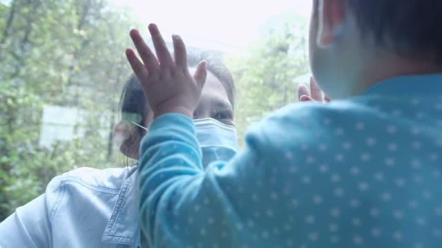 vidéos et rushes de les jeunes femmes portant un masque protecteur et le petit garçon de 12 mois touchent leurs paumes par la fenêtre en verre qui les sépare pendant la distanciation sociale pour empêcher des épidémies de coronavirus ou de réunions de covid-19.famille  - new age concept