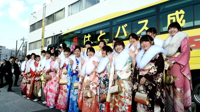 Young women who work as Hato Bus tour guides were dressed to the nines in traditional kimono and fur scarves for a ComingofAge Day ceremony three...