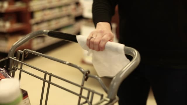 young women wiping supermarket cart handle with sanitizing wipe - moving activity stock videos & royalty-free footage