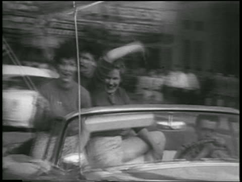 vidéos et rushes de young women with american flag + waving riding in convertible on anchorage street - voiture particulière