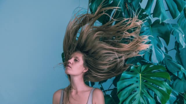 young women with flying hair and monstera - low lighting stock videos & royalty-free footage