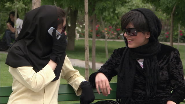 cu young women with friend sitting on bench in park and talking on mobile phone, iran - iran stock videos and b-roll footage