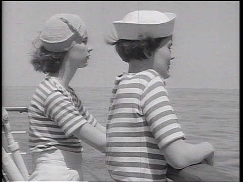 b/w 1934 2 young women with striped shirts leaning on railing of ship + looking out at ocean - 1934 stock videos & royalty-free footage