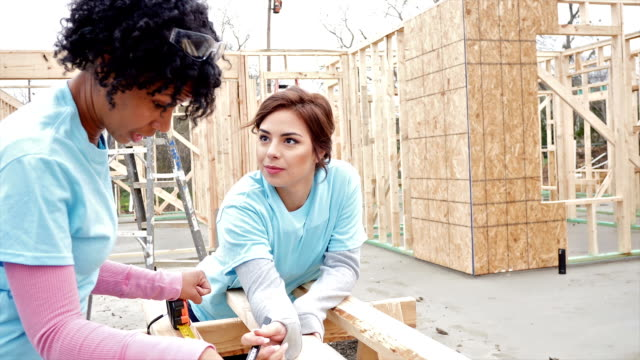 Young women work together measuring in house built for charity