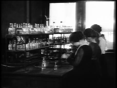 b/w 1920 young women working with bottles in chemistry laboratory / newsreel - anno 1920 video stock e b–roll