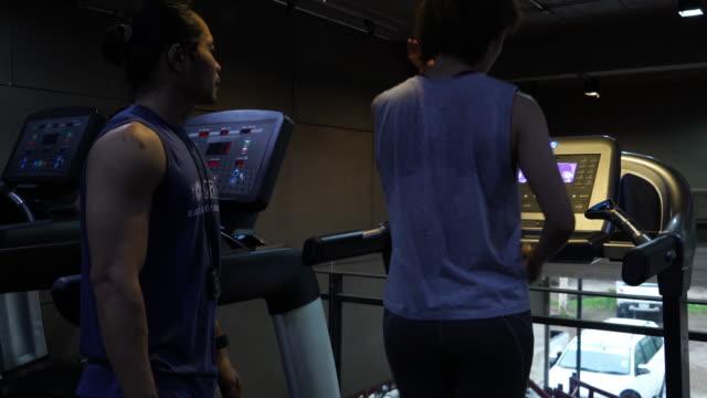 vídeos de stock, filmes e b-roll de treino de jovens mulheres em academia com personal trainer - braço humano