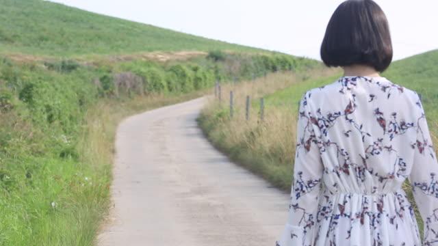 vídeos de stock e filmes b-roll de young women's back wearing a dress and holding hands on the road - articulação humana