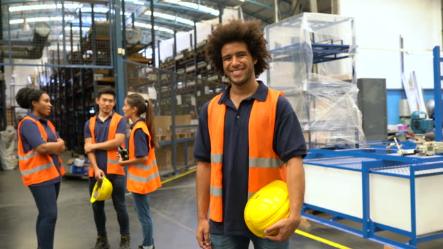 young worker standing in factory warehouse - blue collar worker stock videos & royalty-free footage